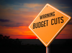 37184085 - budget cuts on warning road sign on sunset sky background.