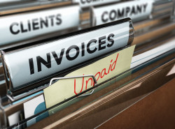 48467259 - close up on a file tab with the word invoice and a note where it is handwritten unpaid with blur effect. concept image for illustration of unpaid invoices recovery.